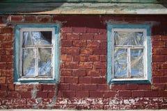 在木制框架的两个窗口在红砖墙壁 库存照片