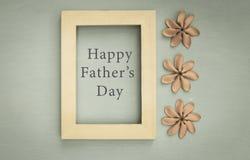 在木制框架的愉快的父亲` s天消息与在木纹理背景的花 库存图片