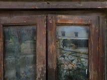 在木制框架的老肮脏的窗口,玻璃反射明亮的黄色花和一个白色大厦,葡萄酒背景装饰 库存图片