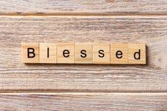在木刻写的保佑的词 在桌上的保佑的文本,概念 免版税库存照片