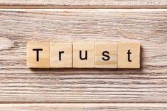 在木刻写的信任词 在桌上的信任文本,概念 库存图片