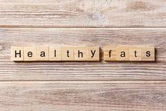 在木刻写的健康油脂词 在桌上的健康油脂文本,概念 库存照片