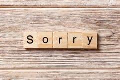在木刻写的抱歉的词 在桌上的抱歉的文本,概念 免版税库存图片