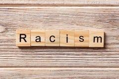 在木刻写的种族主义词 在桌上的种族主义文本,概念 库存图片