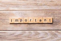 在木刻写的重要词 在木桌您desing的,概念上的重要文本 库存图片