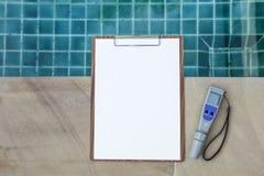 在木剪贴板的空白的白皮书有数字式水测试器的 免版税图库摄影