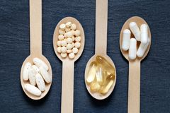 在木匙子的不同的健康补充 免版税库存照片