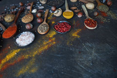 在木匙子的各种各样的印地安香料和金属碗和坚果在黑暗的石桌上 五颜六色的香料,选择聚焦 库存照片