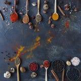 在木匙子的各种各样的印地安香料和金属碗和坚果在黑暗的石桌上 五颜六色的香料,顶视图 免版税库存图片