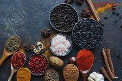 在木匙子的各种各样的印地安香料和金属碗和坚果在黑暗的石桌上 五颜六色的香料,顶视图 免版税图库摄影