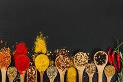 在木匙子的各种各样的香料在黑板岩背景 免版税库存照片