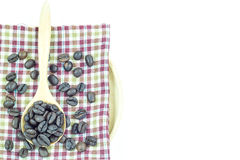 在木匙子的咖啡豆在桌布 免版税库存图片
