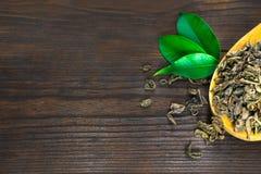 在木匙子的干茶叶有在黑暗的木背景的绿色叶子的 库存照片