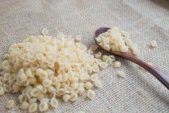 在木匙子的未加工的面团在大袋土气背景 自然和健康食物概念 免版税库存图片