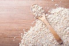 在木匙子的燕麦剥落在燕麦剥落背景 库存图片