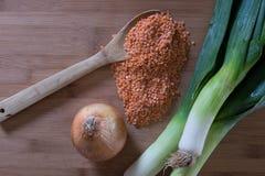 在木匙子的红色小扁豆用韭葱和一棵甜葱 免版税库存图片