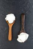 在木匙子的自创椰子产品有黑石backg的 免版税库存图片