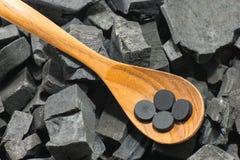 在木匙子的被激活的碳药片在木炭纹理 免版税图库摄影