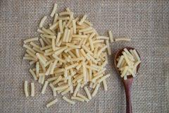 在木匙子的通心面未加工的面团在大袋土气背景 自然和健康食物概念 图库摄影