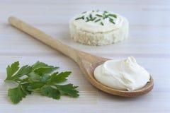 在木匙子的酸性稀奶油在木桌上 免版税库存图片