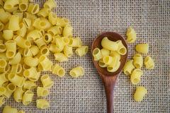 在木匙子的Ditalini未加工的面团在大袋土气背景 自然和健康食物概念 免版税库存照片