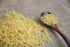 在木匙子的Filini未加工的面团在大袋土气背景 自然和健康食物概念 库存图片