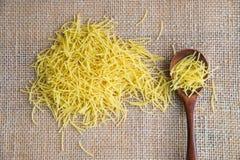 在木匙子的Filini未加工的面团在大袋土气背景 自然和健康食物概念 免版税库存照片