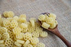在木匙子的Fiori未加工的面团在大袋土气背景 自然和健康食物概念 花形状 免版税图库摄影