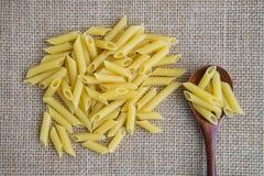 在木匙子的Penne未加工的面团在大袋土气背景 自然和健康食物概念 免版税库存照片