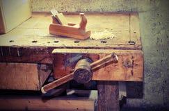 在木匠车间的桌上的老木飞机与 库存图片