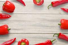 在木厨房书桌上的红辣椒 自由空间在文本或商标促进的中部 免版税库存照片