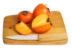 在木厨房切板的柿子 免版税库存照片