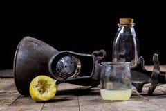 在木厨房用桌上的老生铁汁液机器 柠檬汁和被紧压的柠檬 图库摄影
