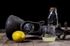 在木厨房用桌上的老生铁汁液机器 柠檬汁和被紧压的柠檬 免版税图库摄影