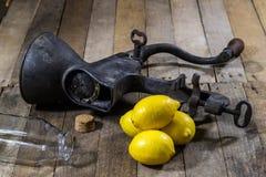 在木厨房用桌上的老生铁汁液机器 柠檬汁和被紧压的柠檬 免版税库存图片