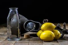 在木厨房用桌上的老生铁汁液机器 柠檬汁和被紧压的柠檬 免版税库存照片