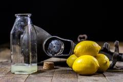 在木厨房用桌上的老生铁汁液机器 柠檬汁和被紧压的柠檬 库存图片