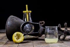 在木厨房用桌上的老生铁汁液机器 柠檬汁和被紧压的柠檬 库存照片