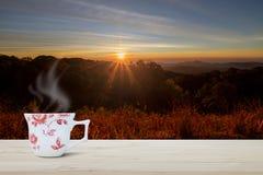 在木台式的热的与阳光的咖啡杯在被弄脏的草甸和山与在日出期间的火光 免版税图库摄影