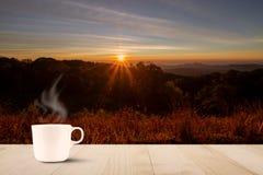 在木台式的热的与阳光的咖啡杯在被弄脏的草甸和山与在日出期间的火光 库存图片