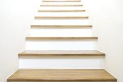 在木和白色墙壁上的白色台阶 免版税库存照片