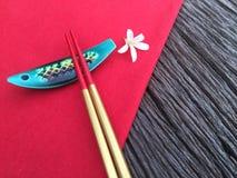 在木和红色桌布的筷子 免版税库存照片