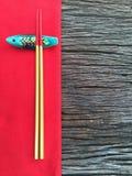 在木和红色桌布的筷子 免版税库存图片