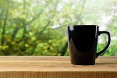 在木和迷离背景的黑杯子 库存照片