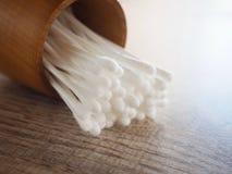 在木圆筒的白色棉花芽在与healthss的概念的桌上 免版税库存图片