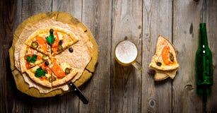 在木圈子、啤酒和一个瓶的薄饼在一张木桌上 免版税图库摄影