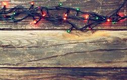 在木土气背景的五颜六色的圣诞灯 减速火箭的被过滤的图象 免版税库存图片