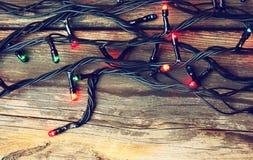 在木土气背景的五颜六色的圣诞灯 被过滤的图象 免版税库存图片