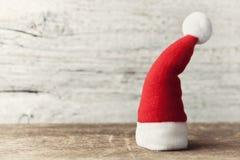 在木土气背景的小的圣诞老人帽子 圣诞节概念新年度 10个看板卡eps问候例证向量葡萄酒 免版税库存照片