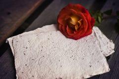 在木土气背景的红色玫瑰与纸 库存图片